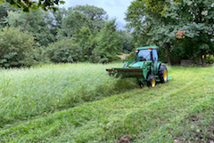 Stewardship tractor mowing a field in summer